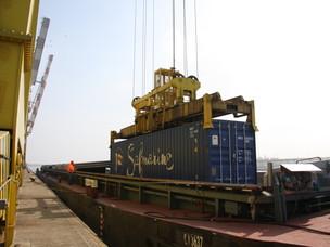 Un container viene caricato su una chiatta al Porto di Venezia